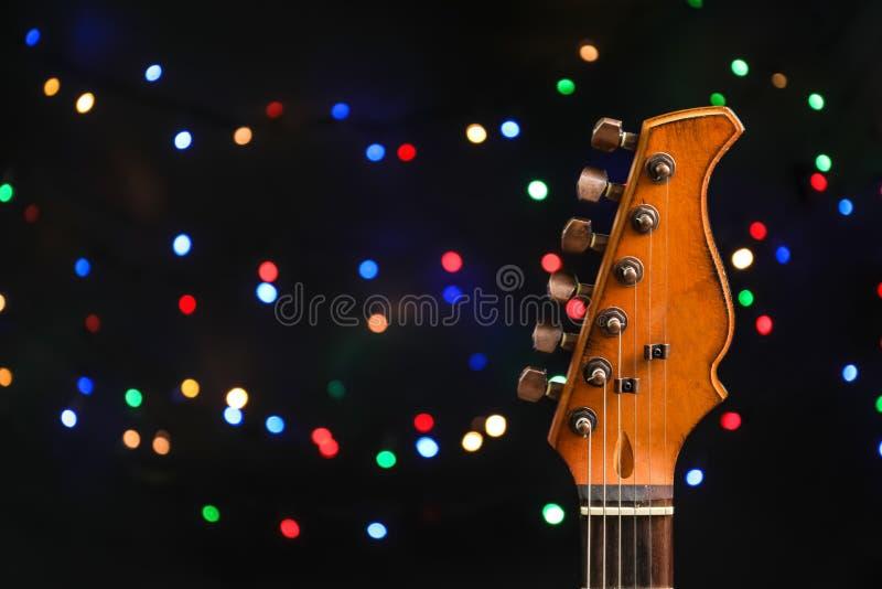 Gitarre gegen unscharfe Lichter Weihnachtsmusik lizenzfreie stockbilder