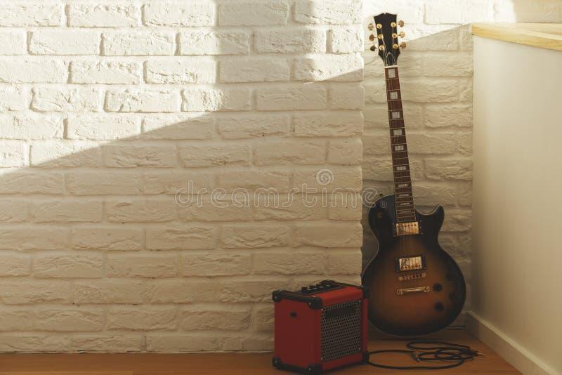 Gitarre im Ziegelsteinraum lizenzfreie stockfotos