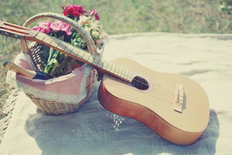 Gitarre, Korb mit Wein und Blumenstrauß von Blumen lizenzfreies stockbild