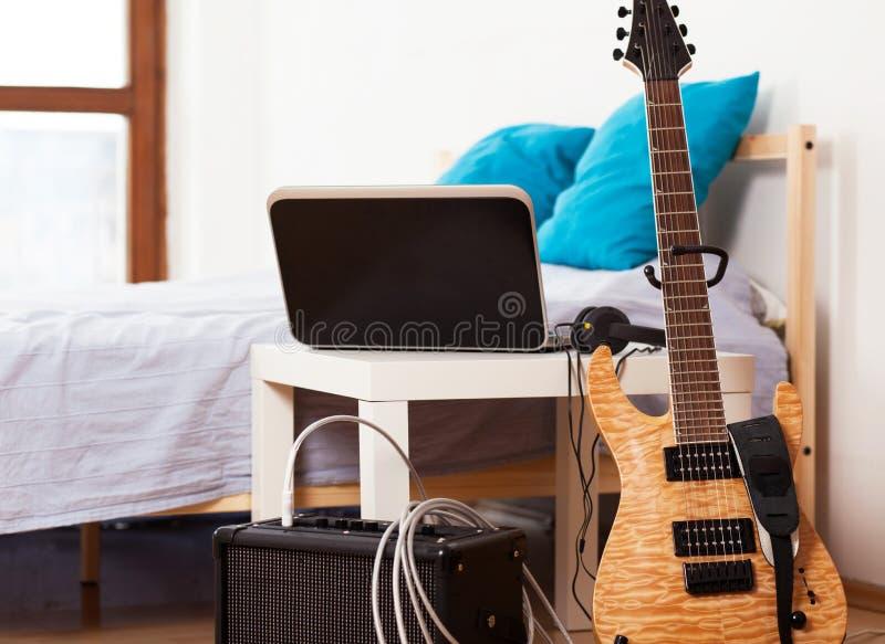 Gitarre mit einem Verstärker zu Hause lizenzfreie stockfotos