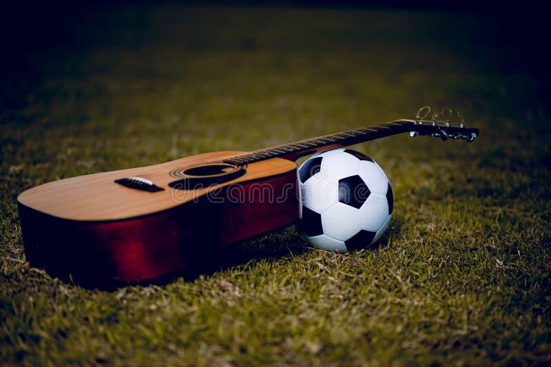 Gitarre und Fußball werden in grüne Rasen gelegt Musik und Sport stockfotos