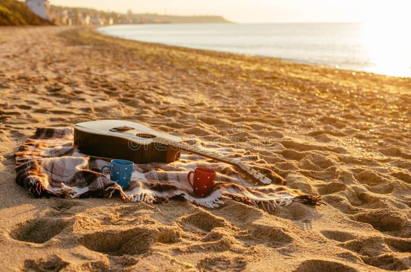 Gitarre und Kaffeetassen auf Strand stockbilder