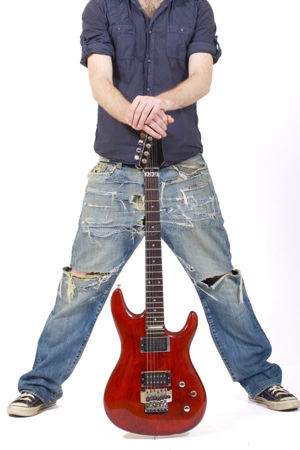 Gitarre zwischen den Fahrwerkbeinen eines Gitarristen stockfoto