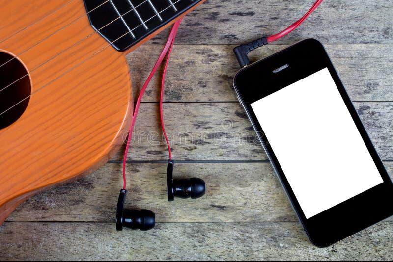 Gitarren hörlurar och ilar telefonen royaltyfri fotografi