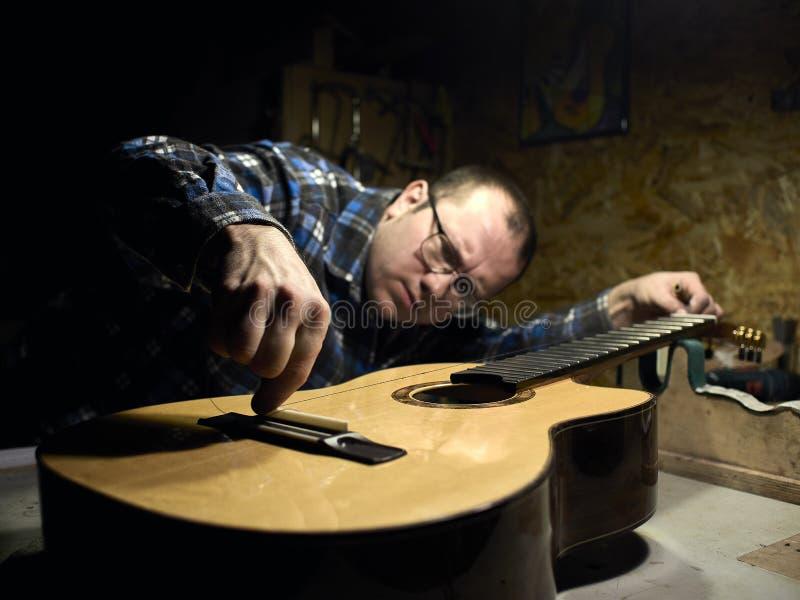 Gitarren Luthiers überprüft die Genauigkeit der Hals- und Satteleinstellung lizenzfreie stockfotografie