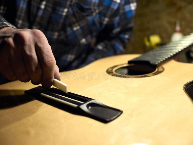 Gitarren Luthiers installiert einen Sattel stockbilder