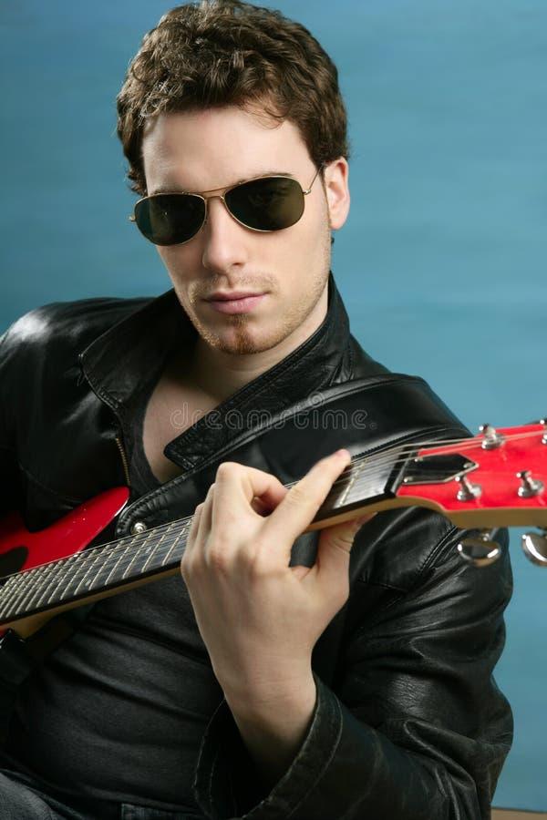 Gitarren-Rockstarmann-Sonnenbrille-Lederjacke lizenzfreie stockbilder