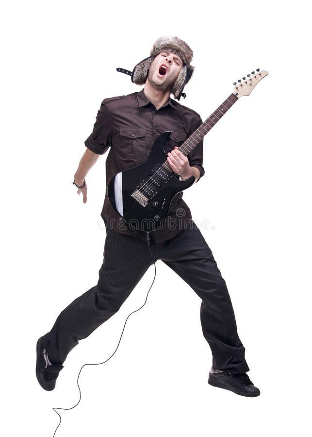 Gitarrenspieler, der in mitten in der Luft springt stockfotografie