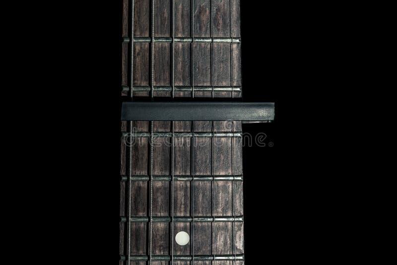 Gitarrenteil, Hals mit Capo auf einem schwarzen Hintergrund lizenzfreie stockfotos