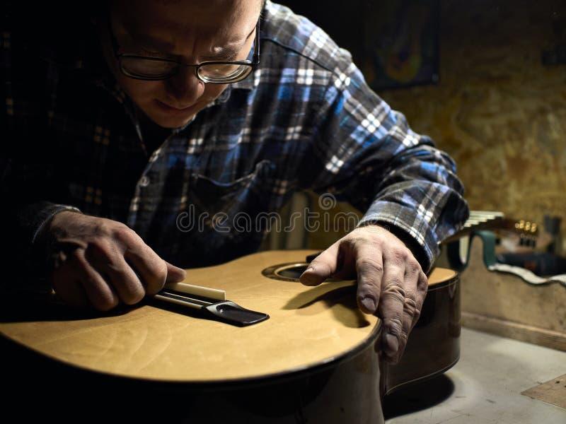 Gitarrer Luthiers installerar en sadel arkivbild