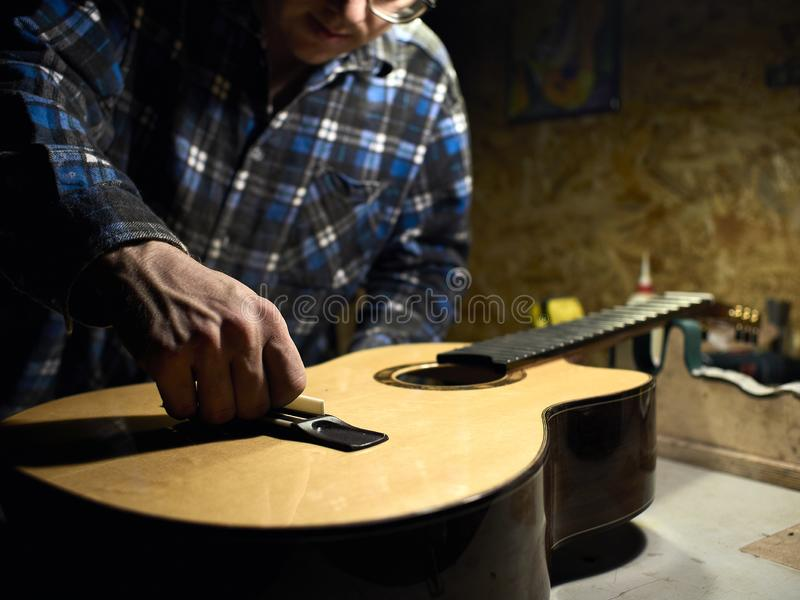 Gitarrer Luthiers installerar en sadel royaltyfria foton