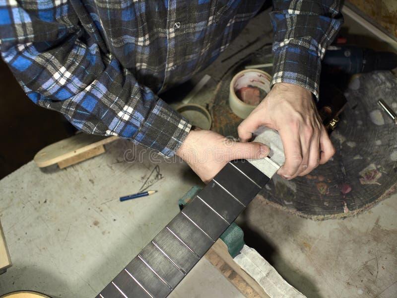 Gitarrer Luthiers installerar muttern royaltyfria bilder