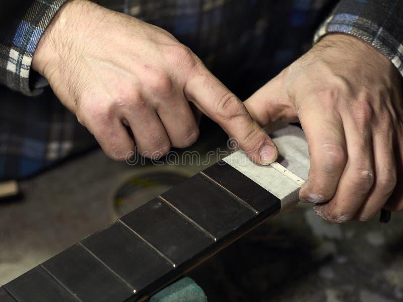 Gitarrer Luthiers installerar muttern royaltyfria foton