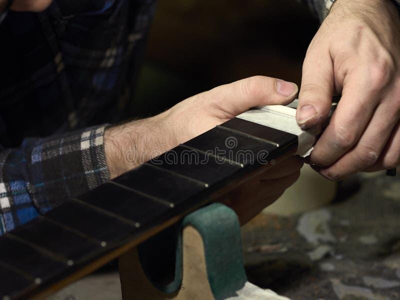 Gitarrer Luthiers installerar muttern arkivbild