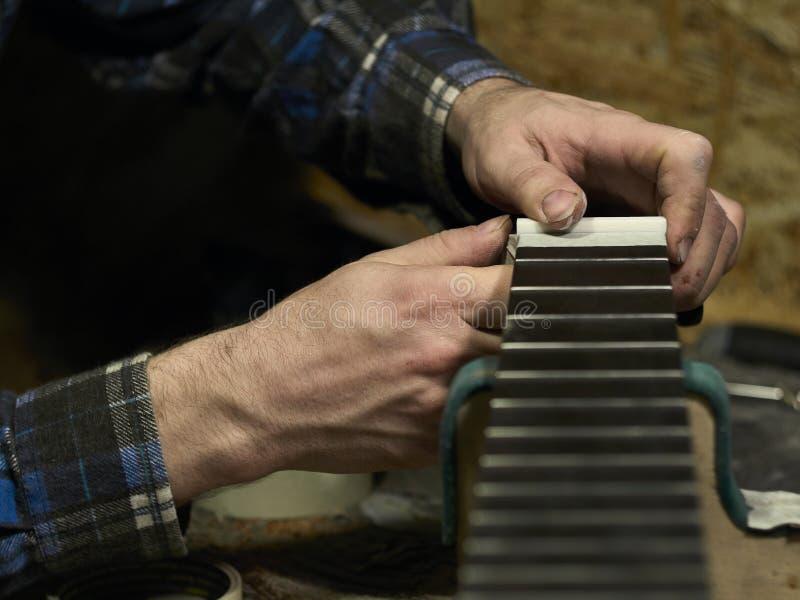 Gitarrer Luthiers installerar muttern arkivbilder