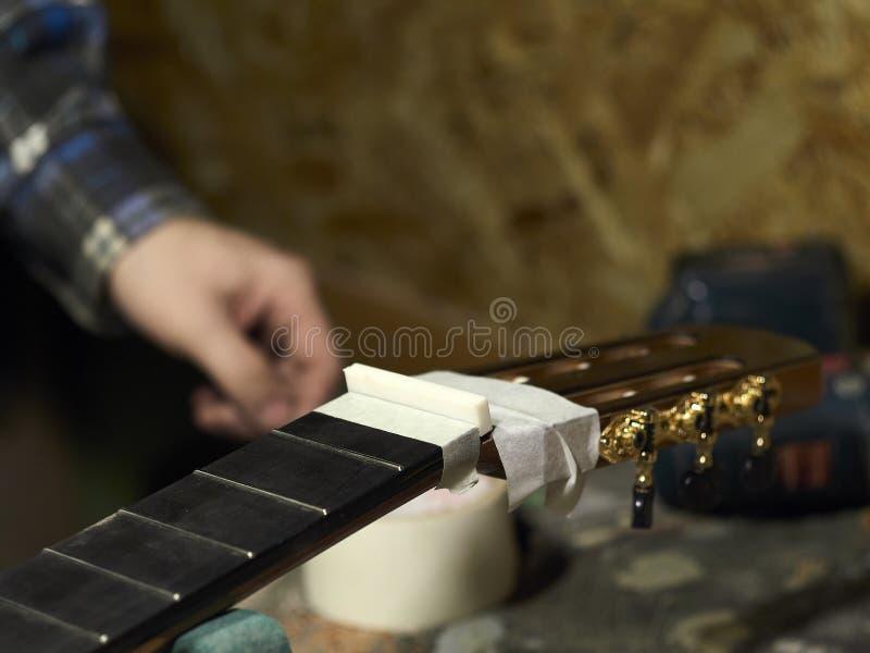 Gitarrer Luthiers installerar muttern arkivfoto