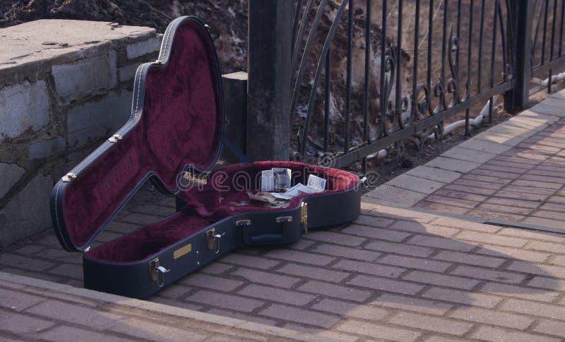 Gitarrfall av en musiker som spelar för pengar royaltyfri fotografi