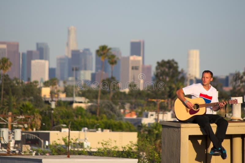 Gitarrist auf Dachspitze mit Los Angeles-Skylinen im Hintergrund lizenzfreie stockbilder
