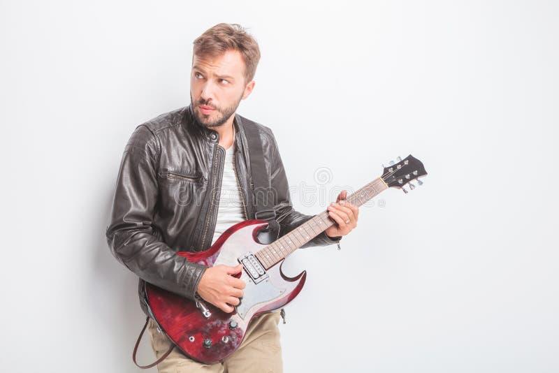 Gitarrist, der eine E-Gitarre und Blicke zu seiner Seite spielt stockbild