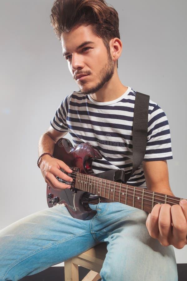 Gitarrist im Studio, das sein Instrument weg schaut spielt stockbilder