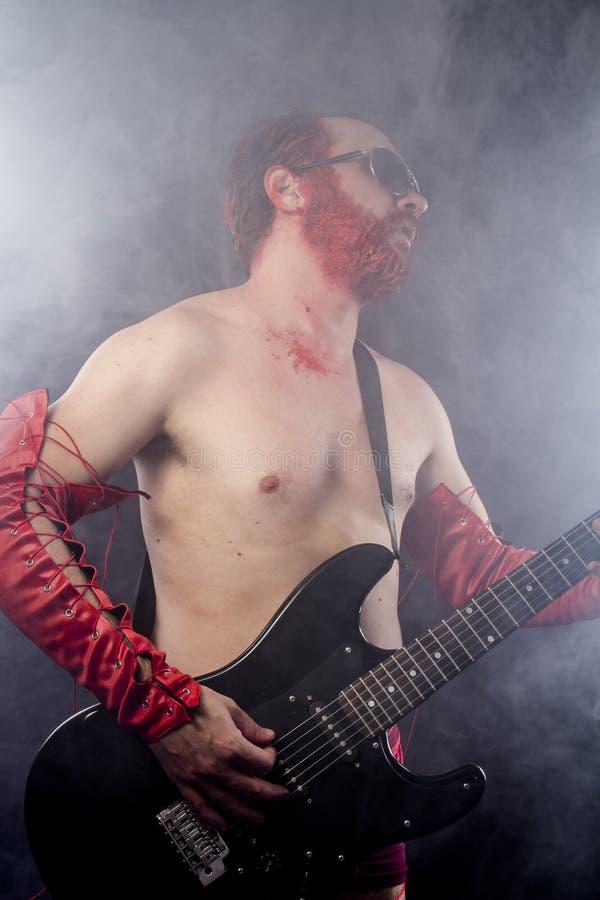 Gitarrist med svart för elektrisk gitarr, bärande framsidamålarfärg och rött royaltyfri bild