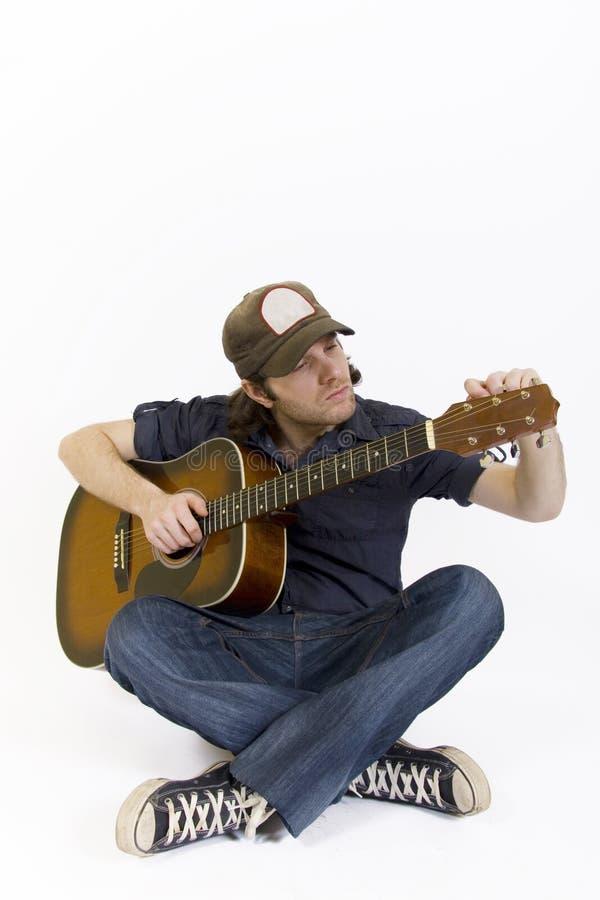 Gitarrist mit der Kalibrierung der Akustikgitarre lizenzfreie stockfotos