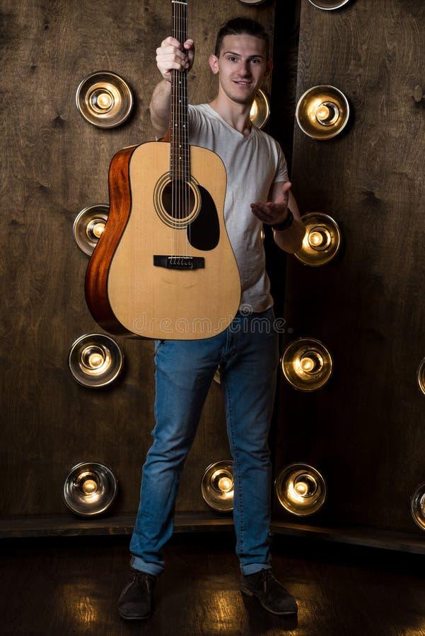 Gitarrist musik En ung grabb står med en akustisk gitarr i hans hand, i bakgrunden med ljus bak honom vertikalt arkivfoton