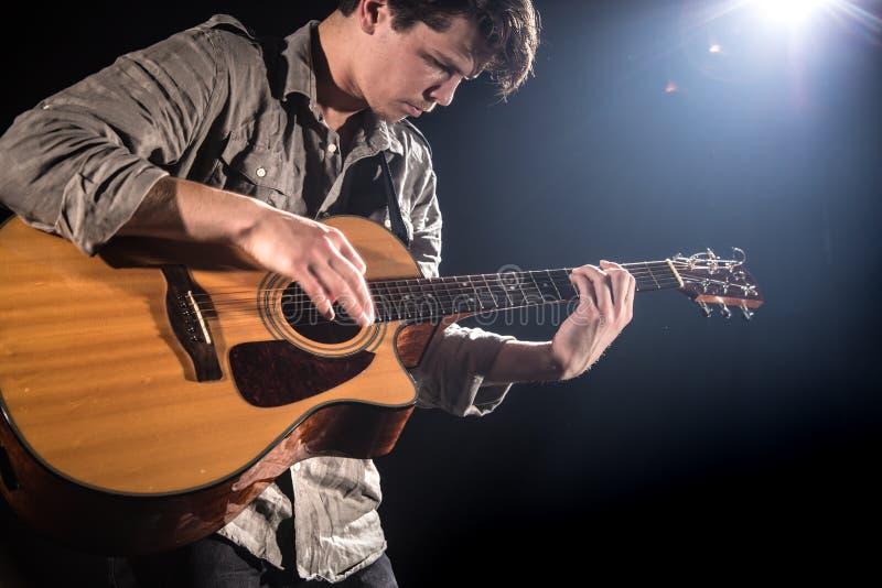 Gitarrist musik En ung man spelar en akustisk gitarr p? en svart isolerad bakgrund arkivbild