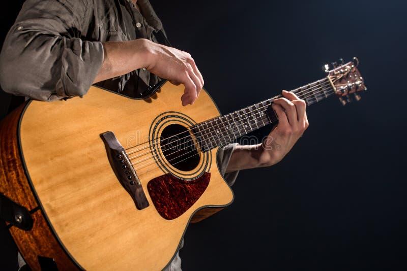 Gitarrist musik En ung man spelar en akustisk gitarr p? en svart isolerad bakgrund royaltyfri bild