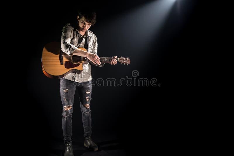 Gitarrist musik En ung man spelar en akustisk gitarr p? en svart isolerad bakgrund arkivfoto