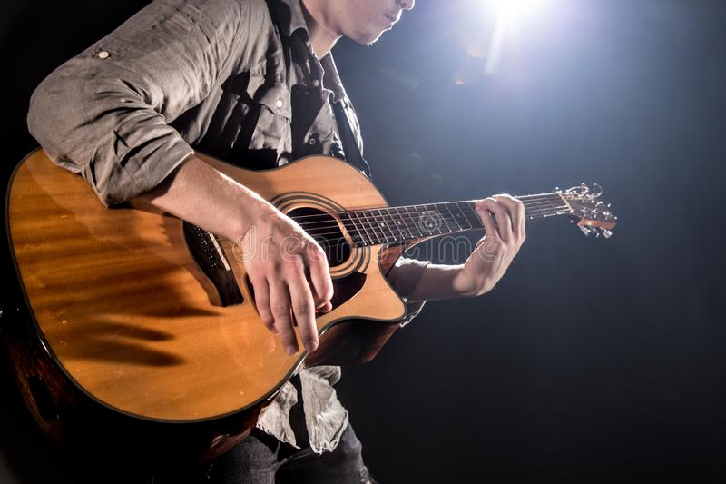 Gitarrist musik En ung man spelar en akustisk gitarr p? en svart isolerad bakgrund royaltyfria bilder