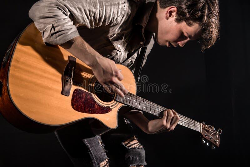 Gitarrist musik En ung man spelar en akustisk gitarr p? en svart isolerad bakgrund fotografering för bildbyråer