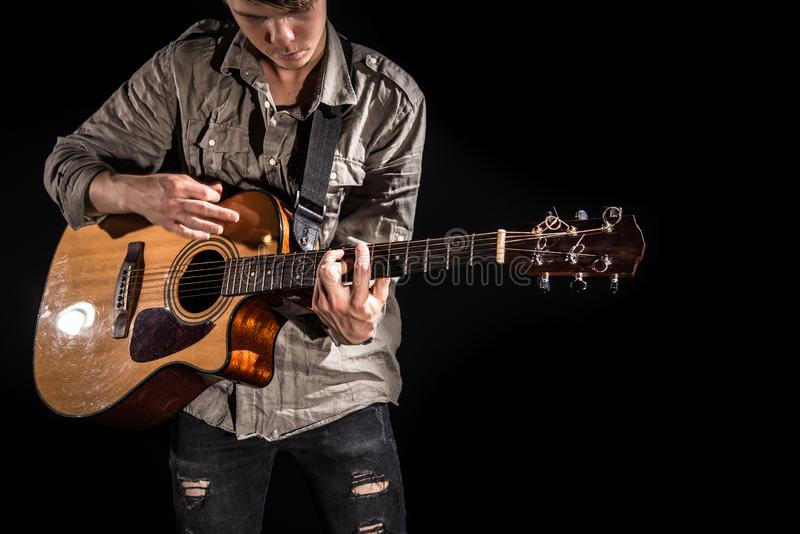 Gitarrist musik En ung man spelar en akustisk gitarr p? en svart isolerad bakgrund royaltyfri foto