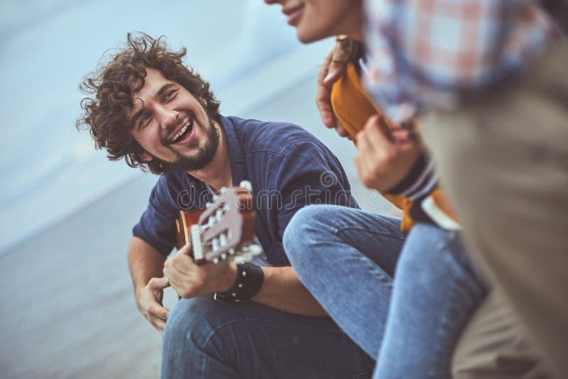 Gitarrist som sjunger en sång till hans vänner royaltyfri bild