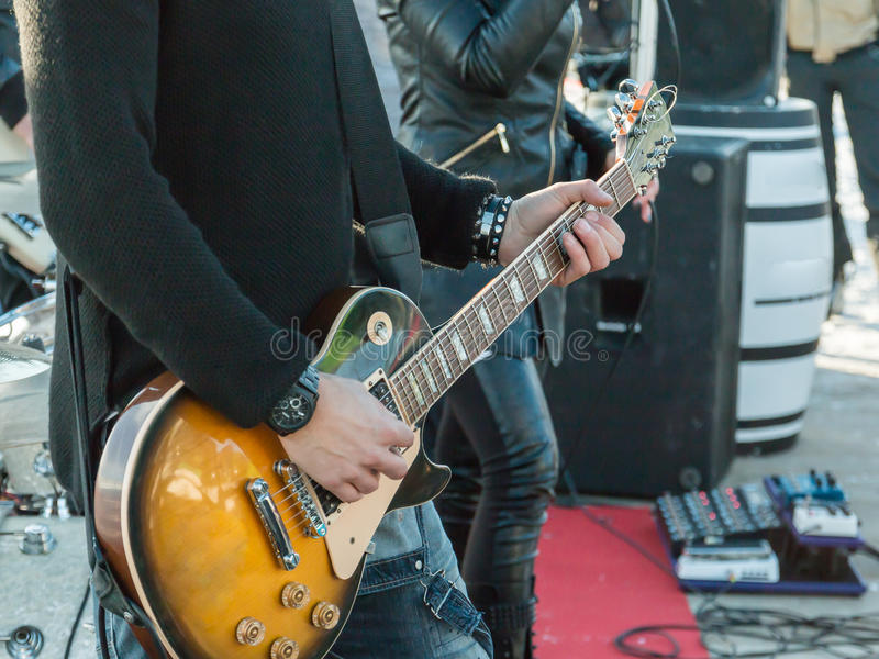 Gitarrist som spelar den elektriska gitarren på en konsert royaltyfria bilder