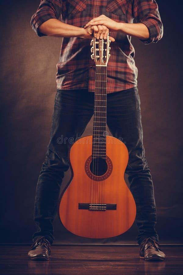Gitarrist steht mit hölzerner Gitarre stockbild