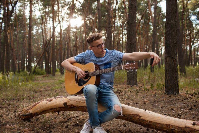 Gitarristen gör selfie vid telefonen i skogen fotografering för bildbyråer