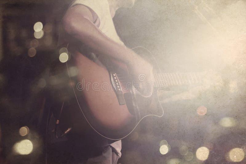 Gitarristen på etappgrungebakgrund, tappning och retro färg tonar royaltyfria bilder
