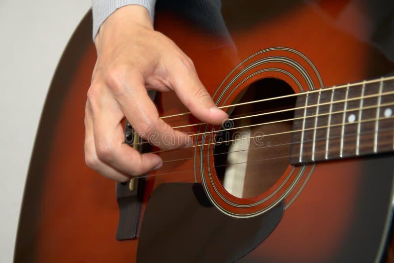 Gitarristhand, Finger, die Akustikgitarre spielen lizenzfreies stockbild