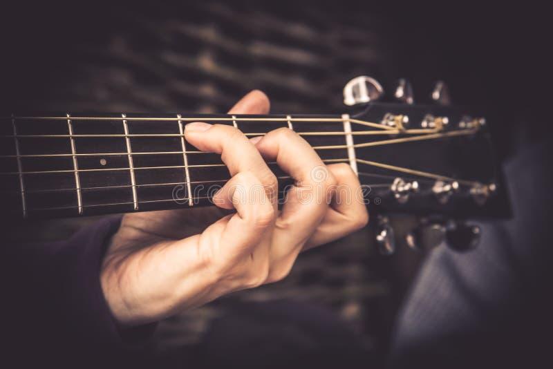GitarristPlaying sång på för fretboardackord för akustisk gitarr stil för tappning royaltyfri bild