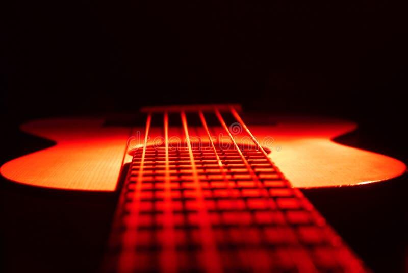 Gitarrukulele på rött ljus arkivfoto