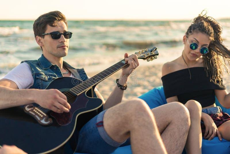 Gitary zabawa Przystojny młody modnisia mężczyzna bawić się gitarę na plaży zdjęcie stock