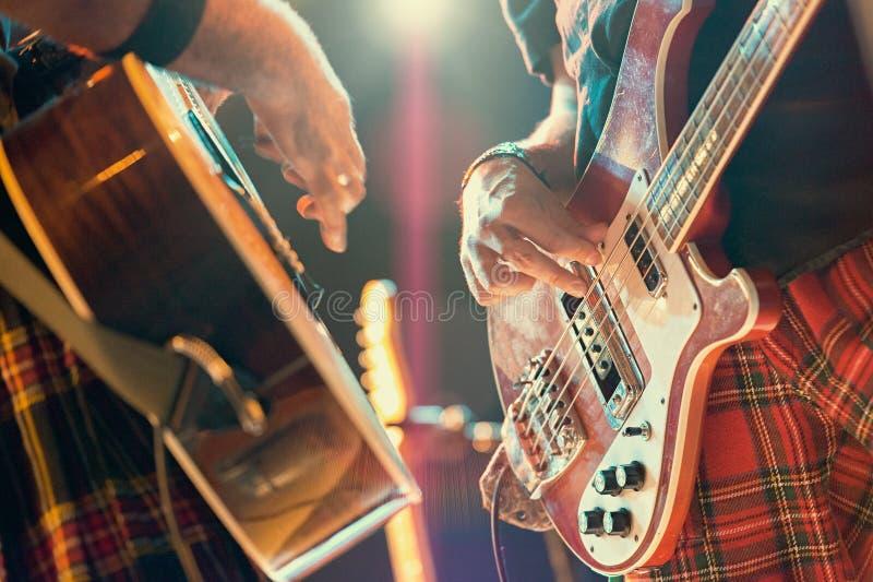 Gitarzysta i basista strzelamy muzyków podczas grupowego występu obraz stock