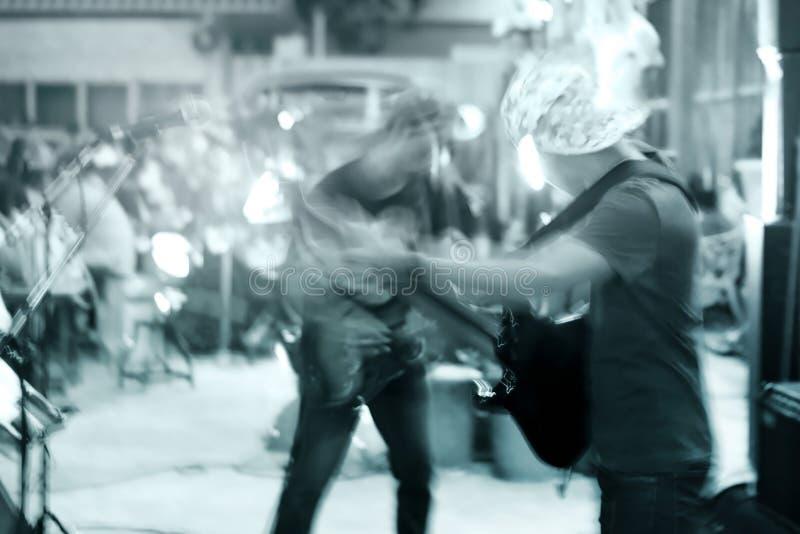 Gitarzysta na ulicznym spacerze przy nocą, błękitny brzmienia i ruchu plamy pojęcie fotografia stock