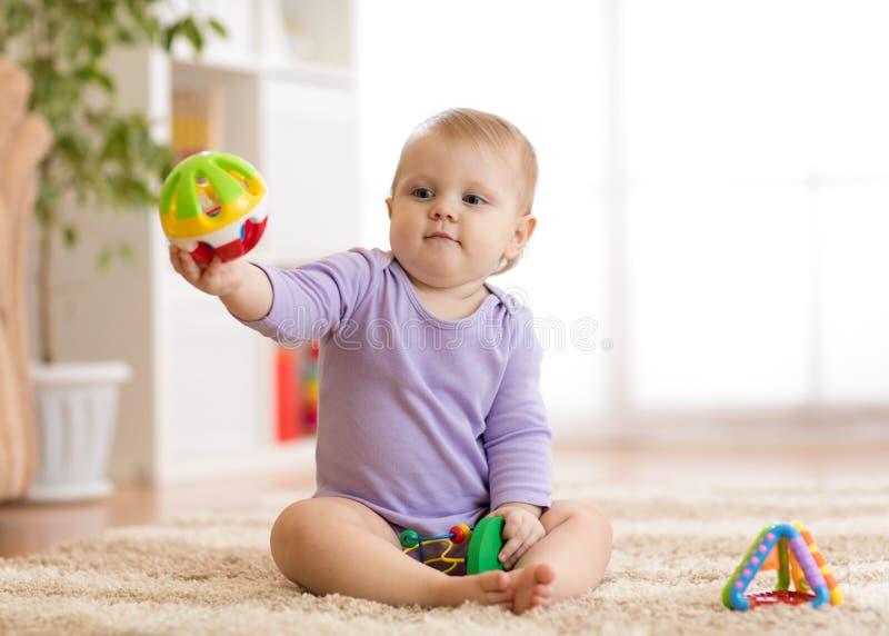 Gitl del bebé que juega en una manta en el piso en cuarto de niños imagenes de archivo
