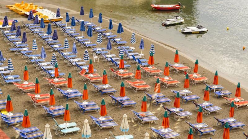 7 GIUGNO 2017, CRETA, GRECIA: sdrai liberi di mattina sulla spiaggia sedie a sdraio variopinte sulla spiaggia sabbiosa del villag fotografia stock libera da diritti