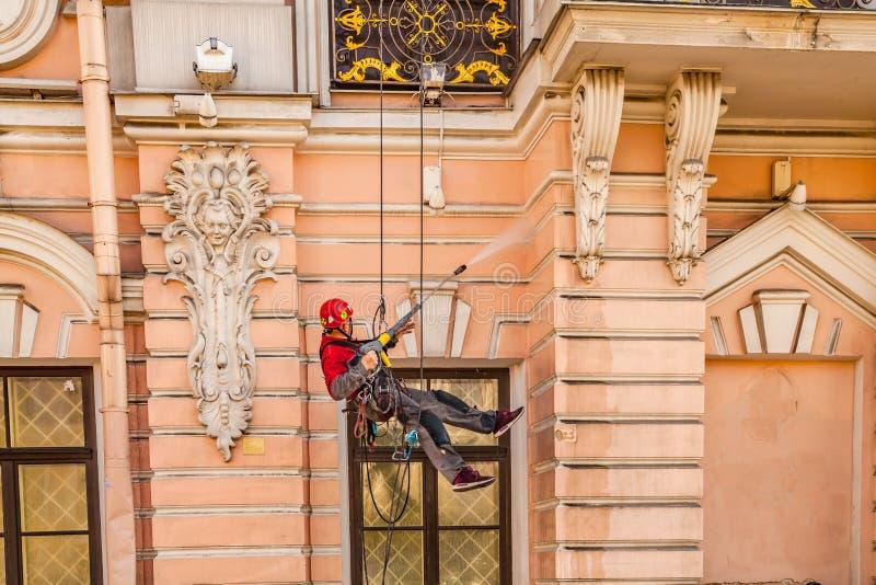 Giugno 2018, St Petersburg, Russia Un lavoratore lava la facciata della costruzione immagine stock
