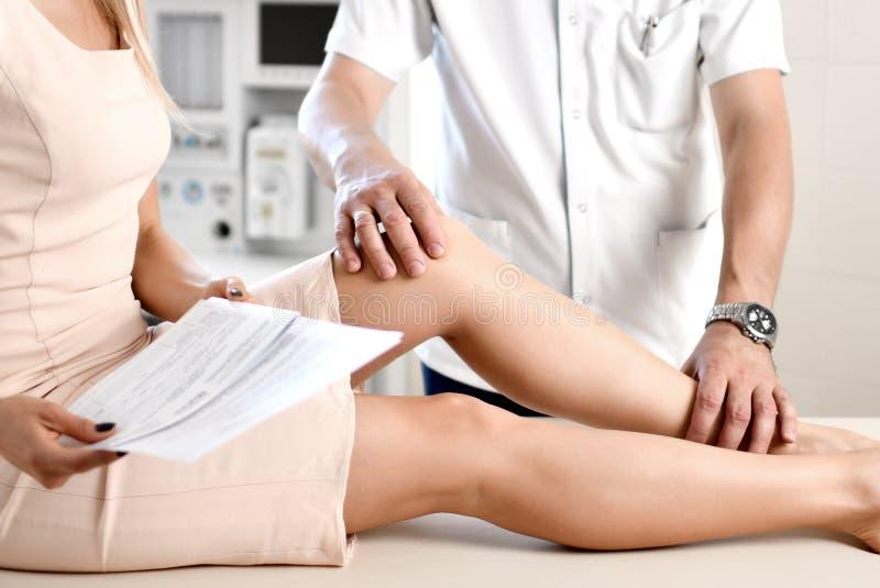 Giunto di ginocchio d'esame del fisioterapista di medico della donna che soffre con il dolore del crampo del ginocchio fotografia stock libera da diritti