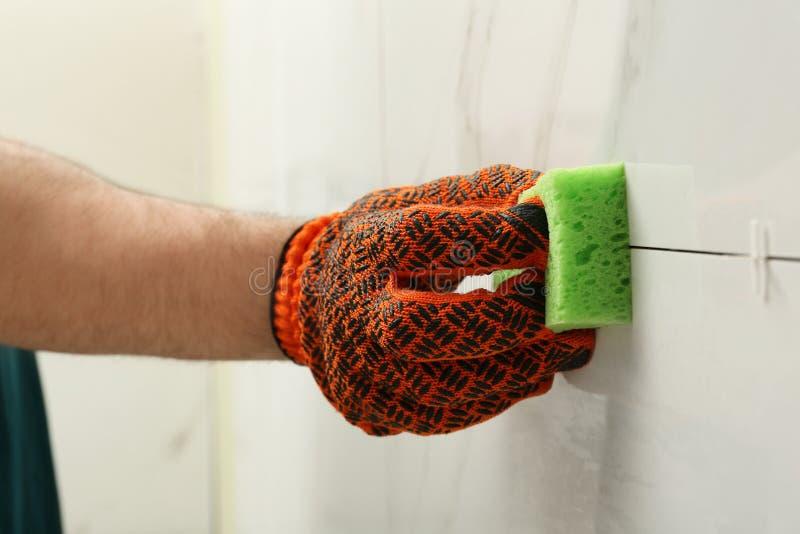 Giunto di pulizia dell'uomo fra le piastrelle di ceramica con la spugna sulla parete, primo piano fotografia stock
