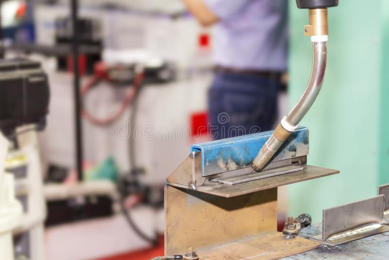 Giunto di T alto vicino di messa a punto dei pezzi in lavorazione sulla tavola per il processo elettrico della saldatura di MIG d fotografia stock
